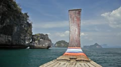 Longtail floats by rocks in the Andaman Sea Stock Footage