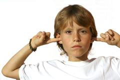 Rebellious child fingers in ears Stock Photos