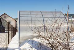 a small greenhouse is made of polycarbonate winter - stock photo