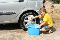 Child washing car helping doing chores Stock Photos