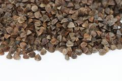 view of scattered dry raw buckwheat - stock photo