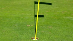 Golf hole on green with flagpole and shadow Stock Footage