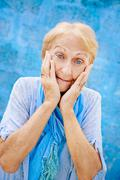 portrait of surprised senior woman with hands on face on blue background - stock photo
