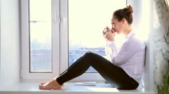 Girl drinks sitting on a window sill, drinks from a cup Stock Footage
