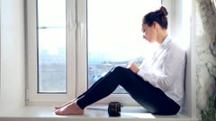 Girl drinks sitting on a window sill,writes to a notepad Stock Footage