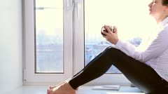 Girl drinks sitting on a window sill Stock Footage