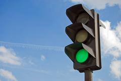 Green color on the traffic light with a beautiful blue sky in background Stock Photos