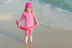 Young child on beach  vacation with sun protection suit and hat. Stock Photos