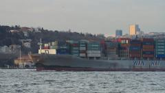 Container ship sails past the city skyline Stock Footage