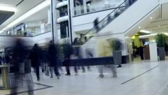 Shoppers moving through busy shopping mall - stock footage