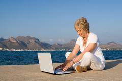 global communication, senior woman on internet on vacation - stock photo