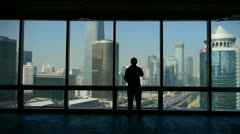 A businessman outlook business building from window. Stock Footage