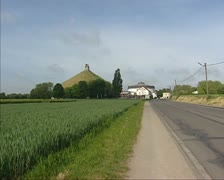 Waterloo Monument (Lions Mound) in rural landscape + road. Stock Footage