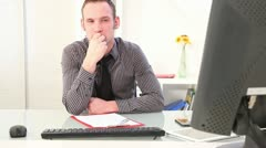 Businessman sits pensively in front of a computer Stock Footage