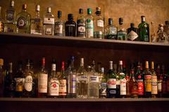 Bar shelves full of alcoholic beverages bottles Stock Photos