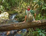 Stock Photo of travelling man sitting on a log near the river in the jungle