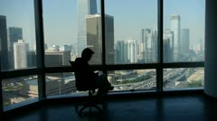 Stock Video Footage of a business human sitting & reading,business building from french window.