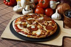 Stone baked meat feast gourmet pizza Stock Photos