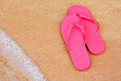 Summer vacation background flip flops on beach Stock Photos