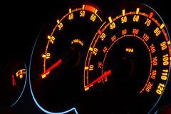 Backlit car dashboard dials glowing at night Stock Photos