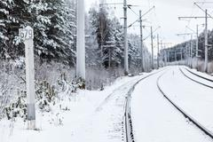 Stock Photo of empty electric mainline railway in winter woods with distance mark