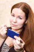 Closeup of pretty caucasian young woman applying pink lipstick at lips Stock Photos