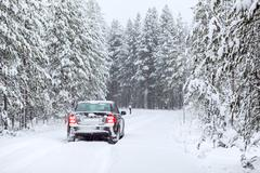 land vehicle driving on a country road in wintry northern forest - stock photo
