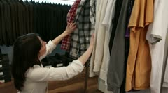 Young woman looking at clothing on rack Stock Footage