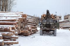 Log loader track with timber in lumber mill in winter season Stock Photos