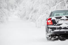 black land vehicle standing on winter road on roadside - stock photo