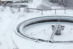 old snow-covered empty round settler in sewerage plant - stock photo