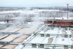 snow-covered aeration tanks in sewerage treatment plant - stock photo