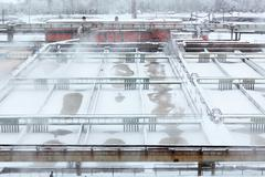 Stock Photo of lot of aeration sewage tanks with evaporation in winter
