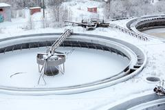 covered with snow round settlers in sewerage treatment plant - stock photo