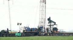 Oil field with rig and workers Stock Footage