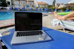 Laptop and a mobil phone beside a pool Stock Photos