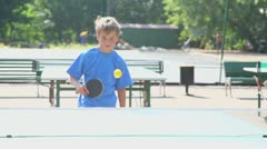 Young boy plays tabletennis with his father at sunny summer day Stock Footage