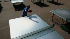 Young boy plays tabletennis at sunny day, view from above Stock Footage