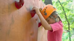 Little girl crawls on pendant wall in outdoor climbing center Stock Footage