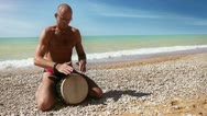 Stock Video Footage of Djembe traditional Drum Player beat rythm on the lonely beach