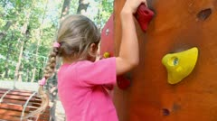 Little girl creeps on pendant wall in outdoor climbing center Stock Footage