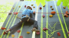 Boy climbs on wall in outdoor climbing center, view from below Stock Footage