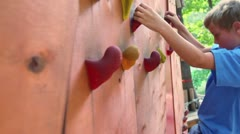 Stock Video Footage of Young boy crawls on pendant wall in outdoor climbing center