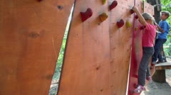 Children creep on pendant wall in outdoor climbing center Stock Footage