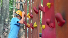 Young boy gets down from wall in climbing center, closeup view Stock Footage