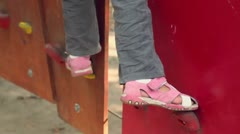 Little girl walks by pendant wall in outdoor climbing center Stock Footage