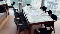 Chairs at table with tableware near window and skyscraper Stock Footage