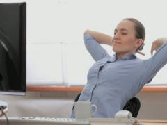 Happy relaxed businesswoman having a break at working place Stock Footage