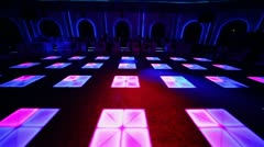 People sit at tables near dance floor in night club - stock footage
