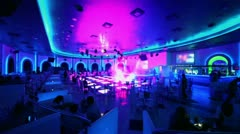People sit at tables of night club with dance floor and bar - stock footage